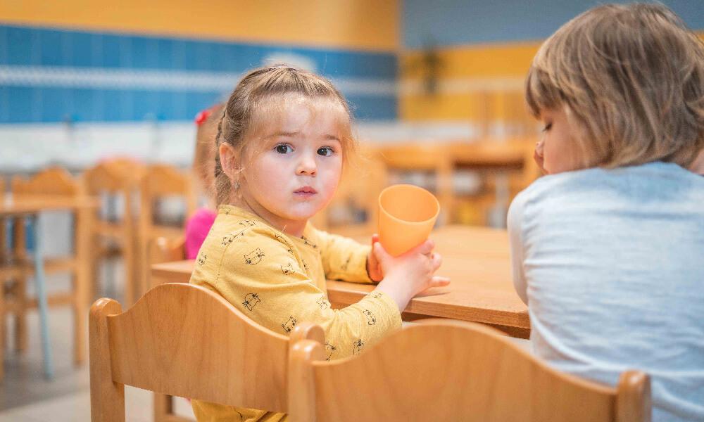 Holčička sedící u stolu s kelímkem od čaje
